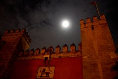 Front gate of moorish fortress alcazar in sevilla. Andalusia, spain, by night with cloudy sky and full moon Stock Photos