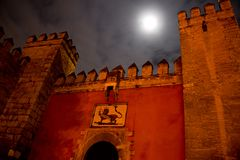 Front gate of moorish fortress alcazar in sevilla. Andalusia, spain, by night with cloudy sky and full moon Stock Photo