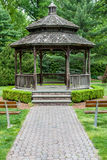 Front of gazebo with wooden benches and paver path. Stock Photo