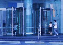 Front of glass office building with glass revolving doors stock photography