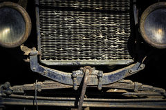 Front grill and headlights of a weathered and rusty vintage car. Stock Photos