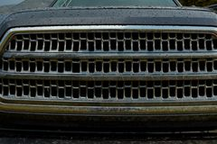 Front grille of a wet 4WD vehicle. Front grille of a wet black 4WD vehicle with mesh design in a close up view Stock Image