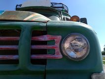 Front headlamp and grill or an old rusty bus with green hood luggage rack on the roof and blank destination board. Front headlamp and grill or an old rusty bus Stock Images