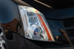 Front headlamp view of black used car stands in the auto showroom sale after washing and polish with orange turn light and bi- stock photos