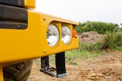Front headlight of heavy machinery. Yellow body color. stock image