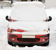 Front headlight of an strange car in winter. Snowfall. This is strange car, red metal in winter Royalty Free Stock Image