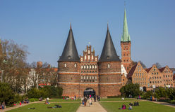 Front of the Holsten gate in Lubeck. Germany with people relaxing in the grass Royalty Free Stock Photo