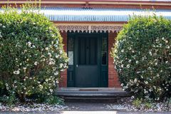 Front house entrance with large green wooden door, bull nose corrugated verandah roof, lace ironwork and two white camellia bushes. Front house entrance with stock photo