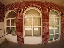Front of the house with wide angle fisheye view. Brick wall and 3 windows with wide angle fisheye view royalty free stock photography