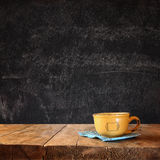 Front image of coffee cup over wooden table and autumn leaves in front and blackboard background with room for text Royalty Free Stock Photo