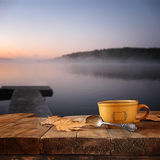 Front image of coffee cup over wooden table in front of calm foggy lake view at sunset.  royalty free stock photography