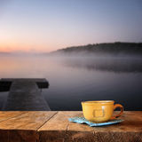 Front image of coffee cup over wooden table in front of calm foggy lake view at sunset.  royalty free stock images