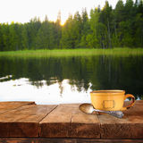 Front image of coffee cup over wooden table in front of lake and forest background Royalty Free Stock Photography