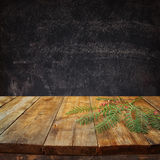Front image of wooden table and autumn leaves in front and blackboard background with room for text Royalty Free Stock Image