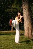 Front kick. A young woman executes a front kick as part of her exercise routine in the park Royalty Free Stock Photos