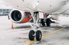 Front landing gear and engine airplane parking in the airport. Front landing gear and engine airplane parking in the airport Royalty Free Stock Images