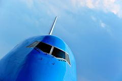 Front of a large passenger airliner. In flight over blue sky Stock Image