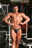 Front lat spread. Training shot of a young man in the gym - posing front lat spread Royalty Free Stock Photography