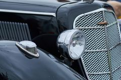 The front light of an old black car stock photography