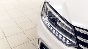 The front lights of the modern white car with LEDs. The car is in the showroom on a sunny day stock photo