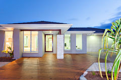 Front of the lights turned on modern mansion with wooden floor a Stock Photos