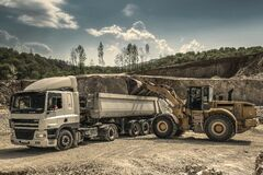Front Load Loader Beside White Dump Truck Stock Photos