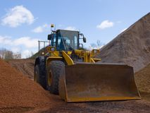 Front Loader. Front-end loader surrounded by hills of dirt and stone Royalty Free Stock Image