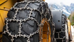 Front loader for snow removal with metal snow chains on wheels. Snow removal in the mountains. royalty free stock images