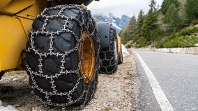 Front loader for snow removal with metal snow chains on wheels. Snow removal in the mountains. stock photos
