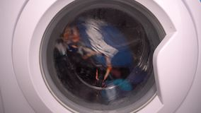 Front loading washing machine in action. With colored cloths in the drum stock video