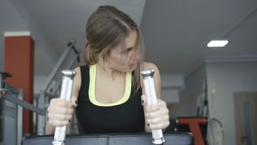 Front look of girl working out with simulator for legs and buttocks muscles 4K stock video footage