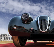 Front low angle view of a classic old-timer vintage sports car. Front low angle view of an unknown old-timer retro vintage sports car under blue cloudy sky. The Royalty Free Stock Photos