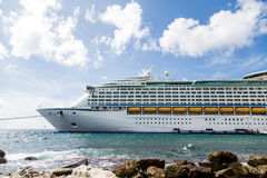 Front of Luxury Cruise Ship Moored Beyond Rocks Stock Images