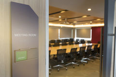 Front of meeting room with tag status vacant and Fire alarm notification wooden table sunlight from window.  Royalty Free Stock Image