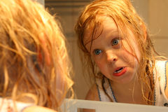 In front of the mirror. Little girl making faces in front of the mirror in golden-orange light Royalty Free Stock Images