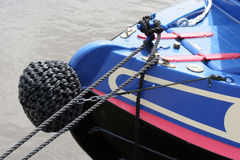 Front of a Narrowboat. Front end of a narrowboat with black ropes attached / moored to river bank Stock Photo