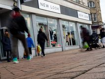 The front of a New Look store with people caught blurred in motion. Pedestrians blurred in motion walking past a New Look shop in Bournemouth, Dorset, England Stock Image