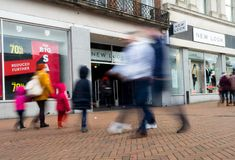 The front of a New Look store in the UK showing logo and shop windows with sale signs and blurred pedestrians walking past. A New Look store with sale signs in Stock Image