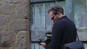 Video maker looking for subject to shoot in front of an old door SF. In front of an old door in an ancient town a video maker is looking for the right shot stock video footage