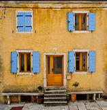 Front of an old house with blue shutters Royalty Free Stock Photography