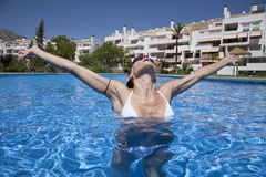 Front open arms woman in a pool. Front open arms woman with black goggles in a blue pool Royalty Free Stock Images