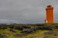 In front of orange lighthouse. The car in front of orange lighthouse  on the rocks in Iceland Royalty Free Stock Images