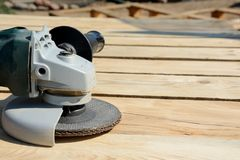 Front part of angle grinder with abrasive disc on planks Stock Photo