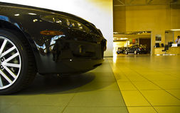 Front part of car in showroom. View of front part and wheel of black car in showroom royalty free stock photography