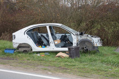 Front part of a crashed car wreck on the side of the road Stock Photos