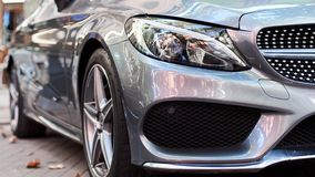 Front part of a grey car. Front part of a new grey luxury car on the street stock photography