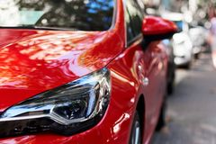 Front part of a red car. Front part of a new red luxury car on the street stock photo