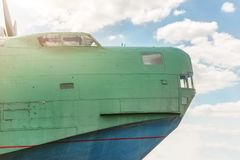 Front part of old amhibian plane against blue sky. Vintage anti-submarine military hydroplane aircraft . Toned Stock Image