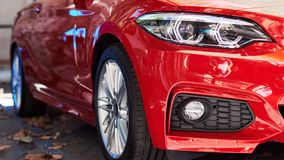 Front part of a red car. Front part of a new red luxury car on the street stock photography