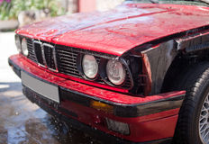 Front part of red car without wing with water drops on car wash.  Royalty Free Stock Images